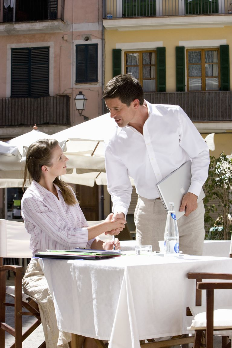 Man and woman shaking hands at sunny, outdoor cafe