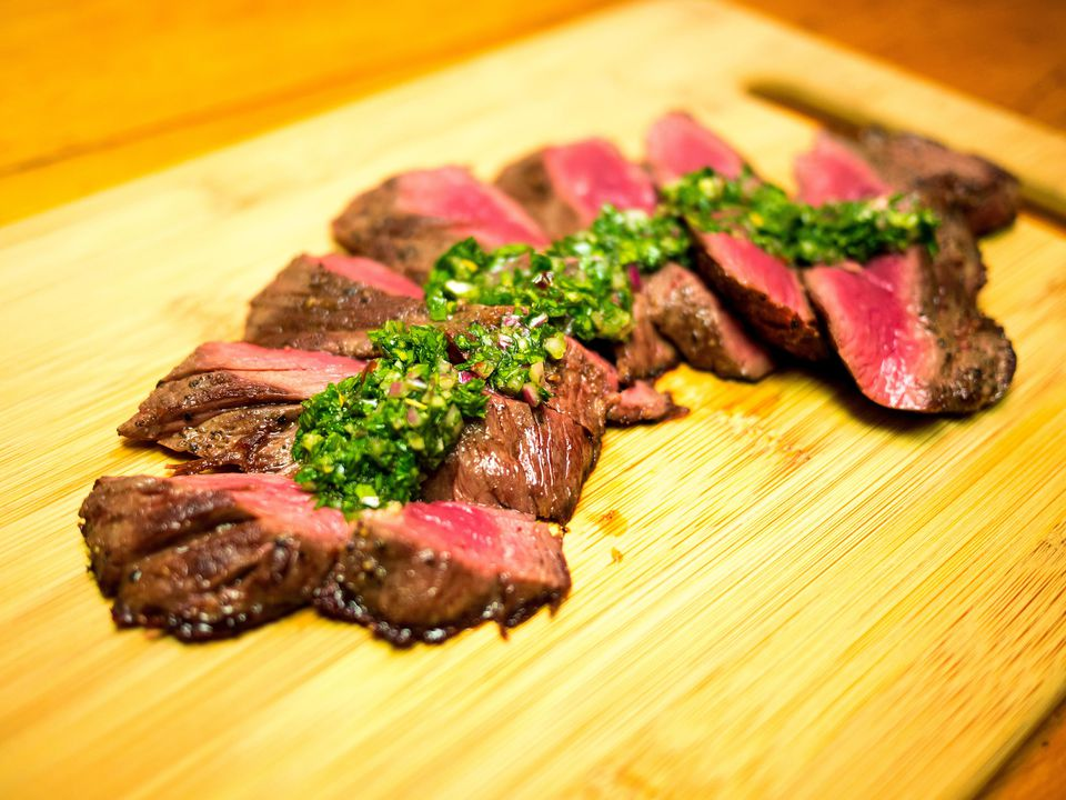Hanger Steak sliced on a cutting board with a green sauce on top