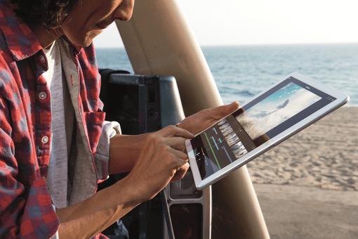 A man using an iPad Pro at the beach.