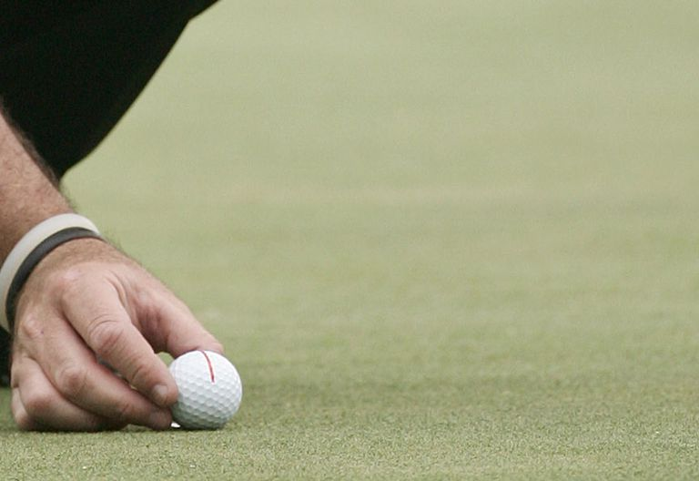 Red line drawn on golf ball to help golfer with alignment and aim