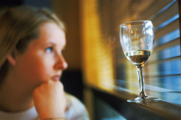 Worried woman looking out window with glass of wine on windowsill