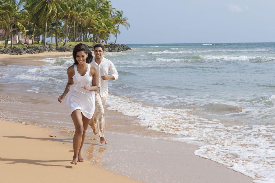 Hispanic couple running along the shore of LaPared Beach, Luquillo, Puerto Rico, United States of America