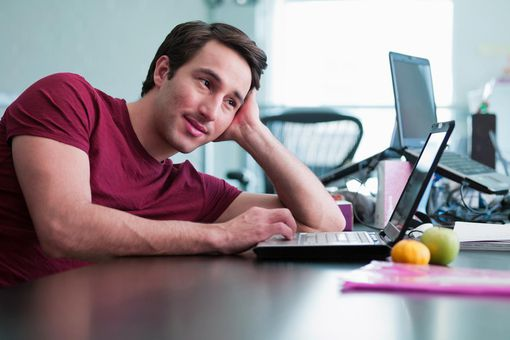 Smiling businessman using laptop and leaning on desk in office