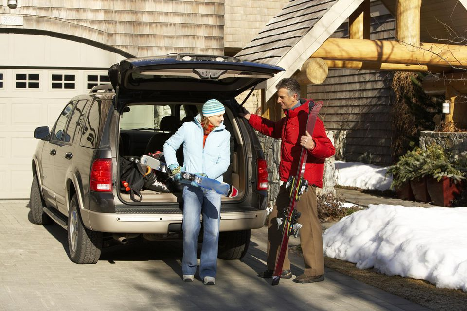 Man and woman in driveway loading car to go skiing.