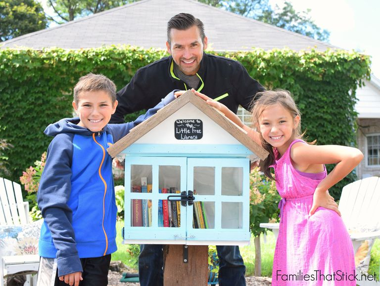 A family standing by a little free library that they built