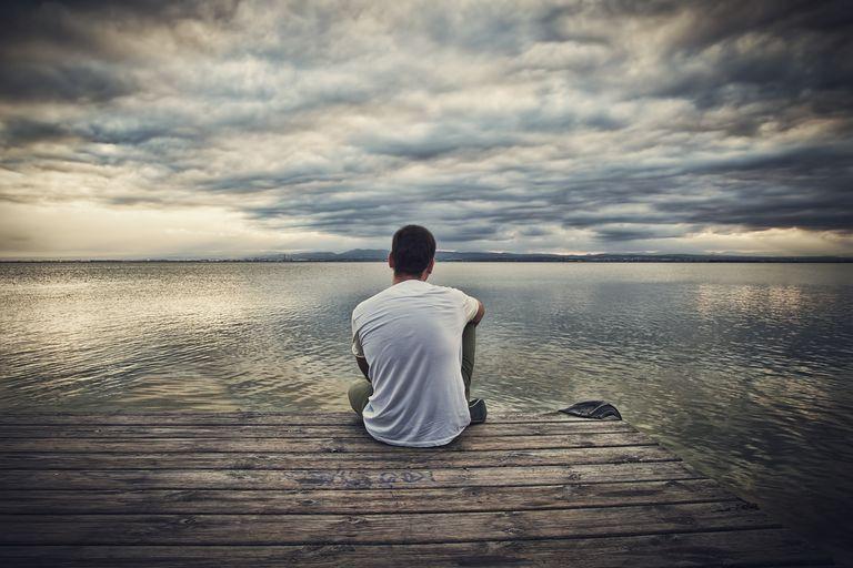 Hombre sentado al frente de un lago