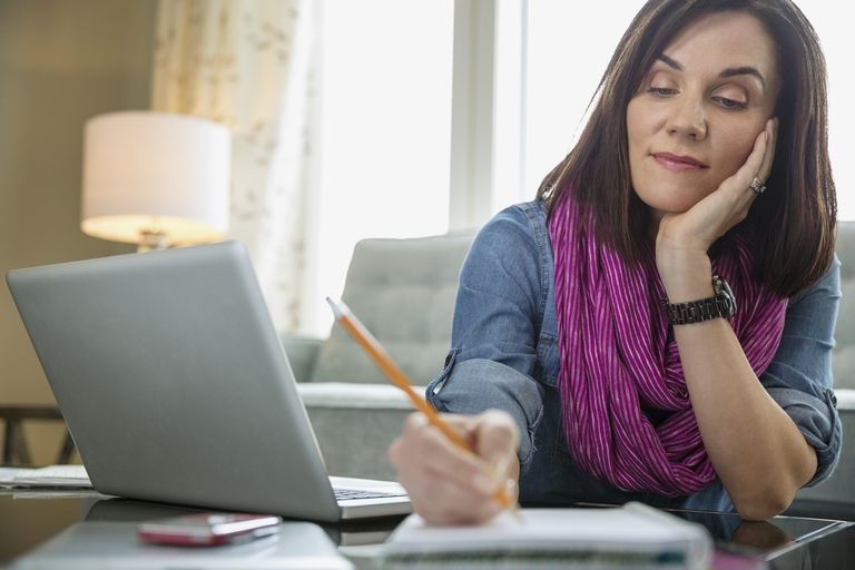 Woman writing on notepad in front of computer
