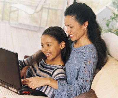 A mom and daughter use the computer together