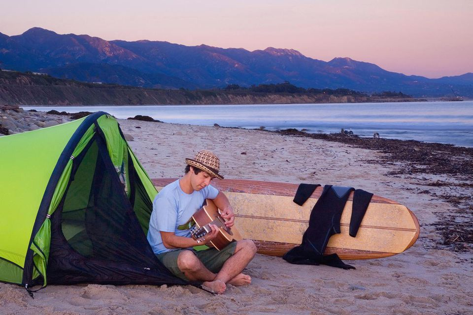 A young man with a guitar sits near his tent while camping on the beach waiting for surf.
