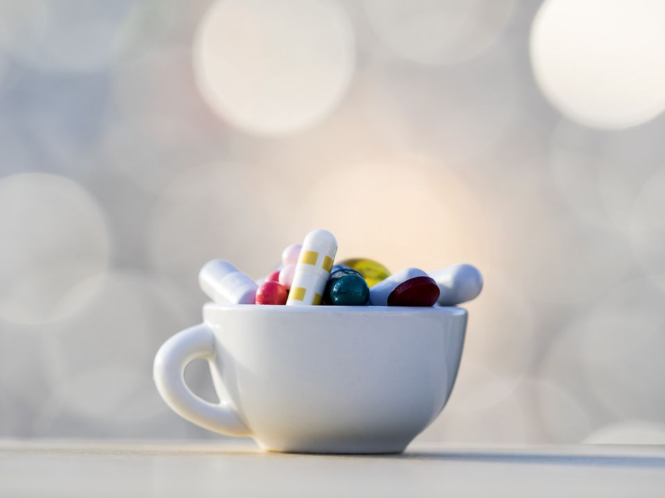 A coffee cup full of pills
