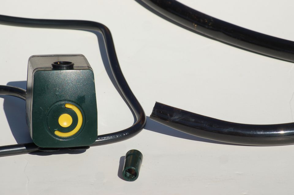 Closeup showing (from left to right) the pump, adapter, and plastic tubing.