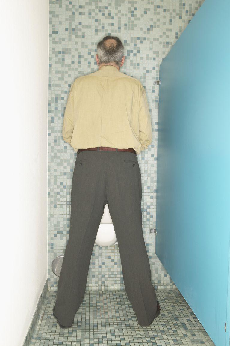 Businessman Using Urinal