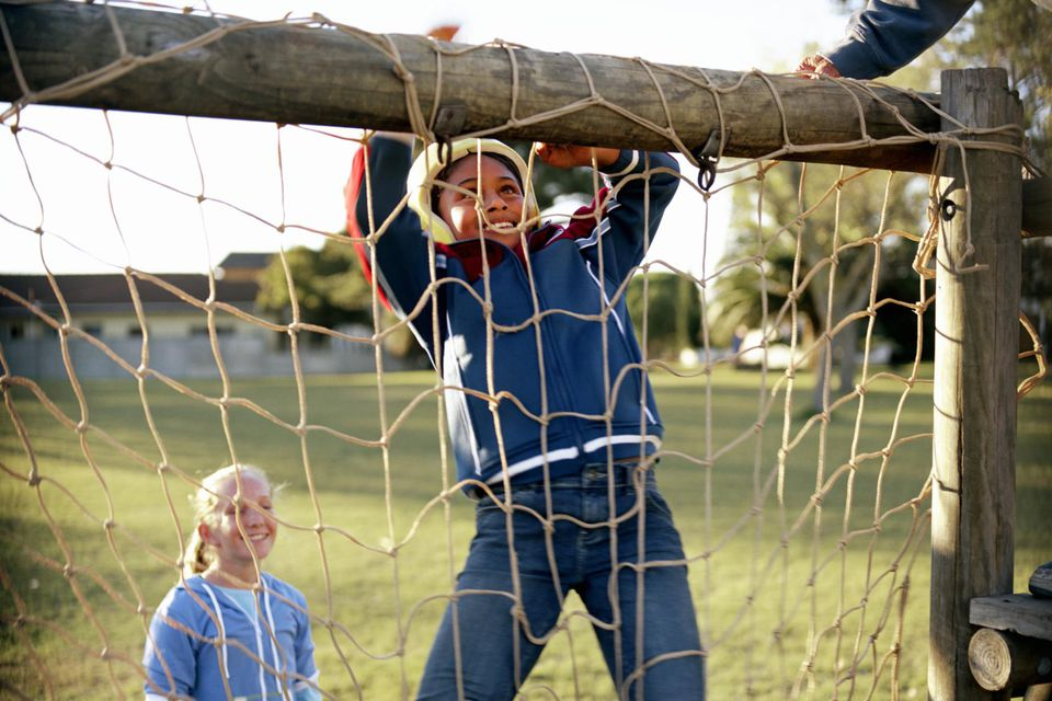 Girl (9-11) climbing obstacle in adventure playground