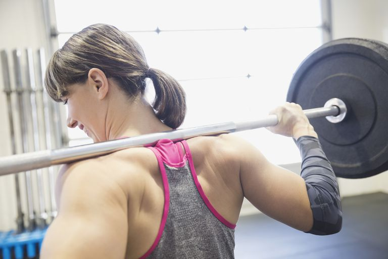 Woman with barbell on her shoulders