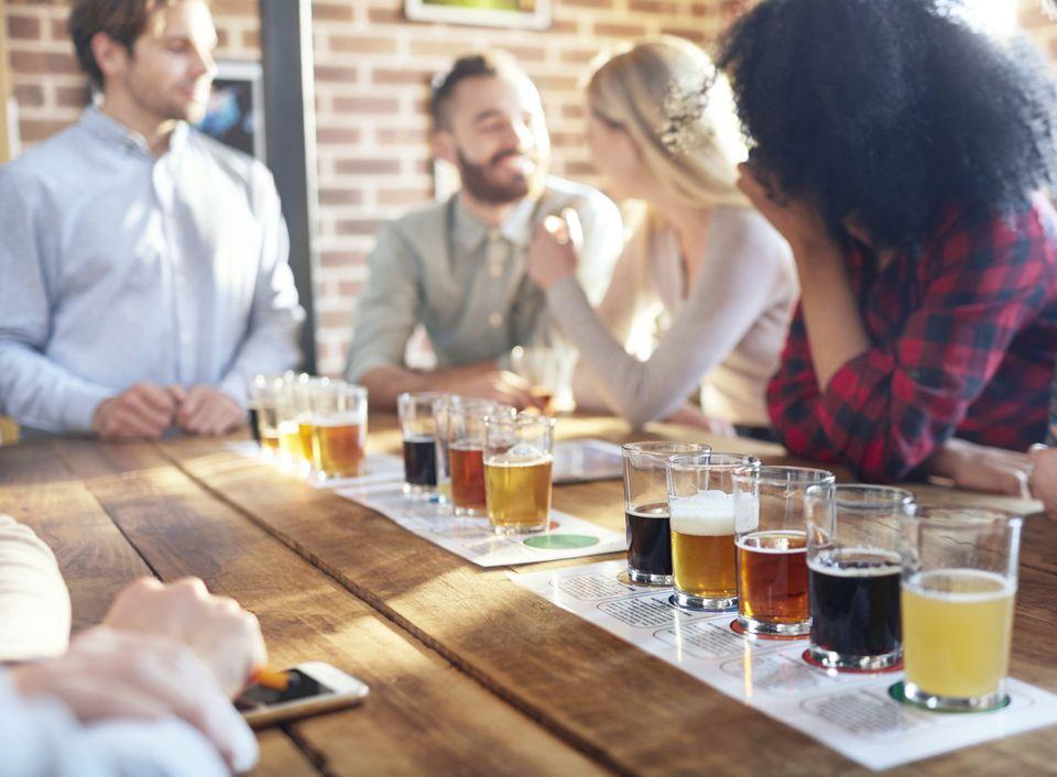 Friends tasting beer samples at brewery