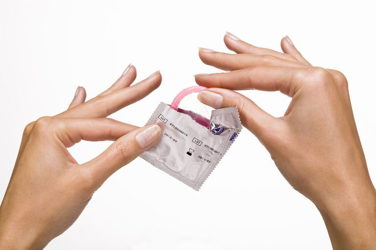 Woman's hands holding a condom