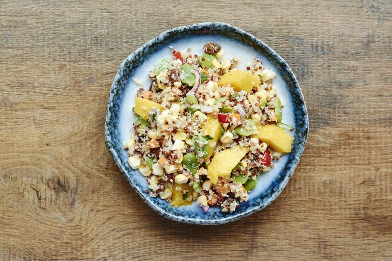 Quinoa salad with mango, carrots, fava beans, red bell pepper, red onion, corn, coconut and raisins