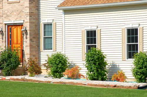 The foundation shrubbery in this photo is nicely set off by a white stone mulch.