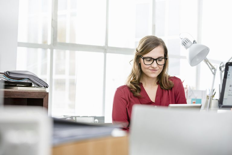 A picture of a woman at a desk working on her computer