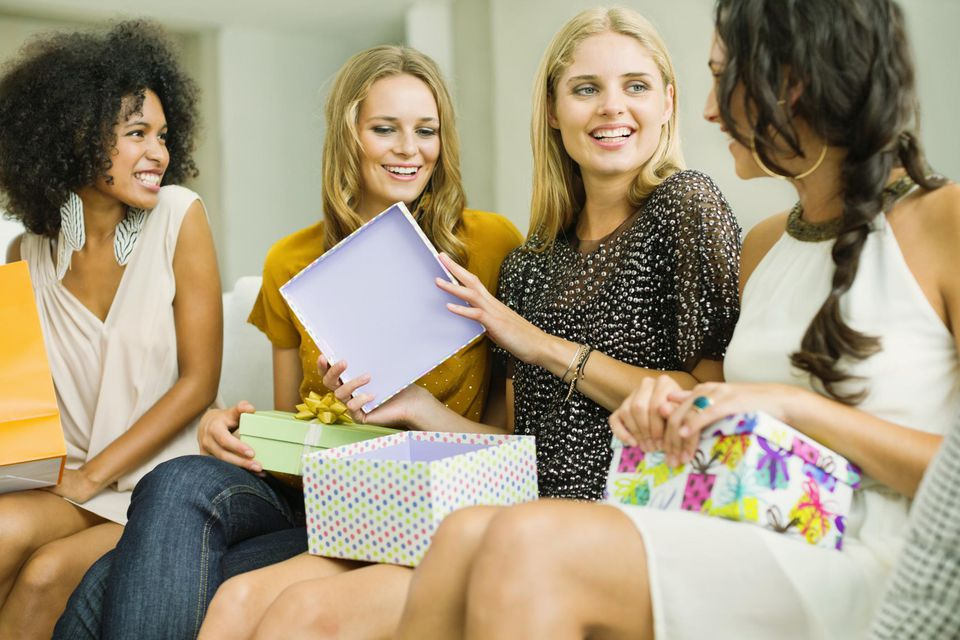 Woman opening gifts at a get-together with friends