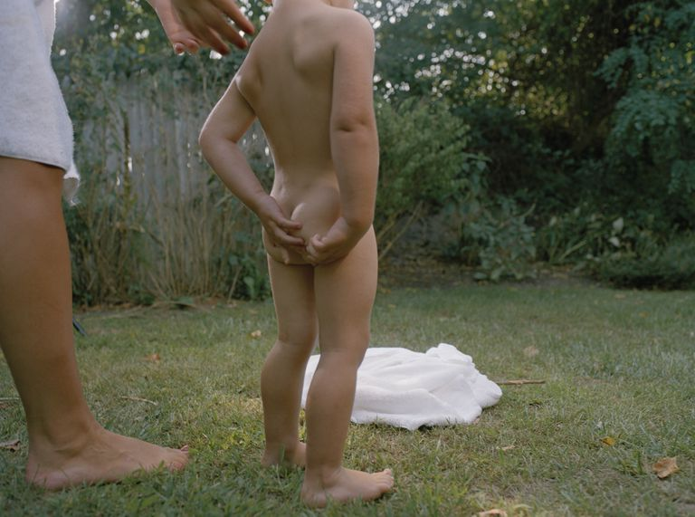 Naked boy (2-4) scratching buttocks, rear view