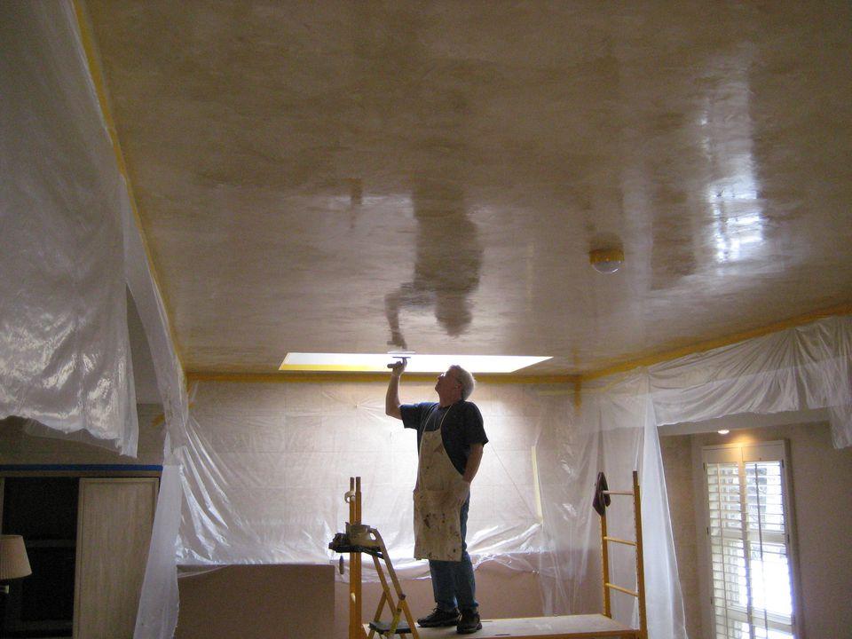 man applying Venetian plaster to ceiling