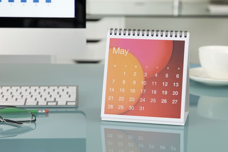 may calendar next to computer on desk
