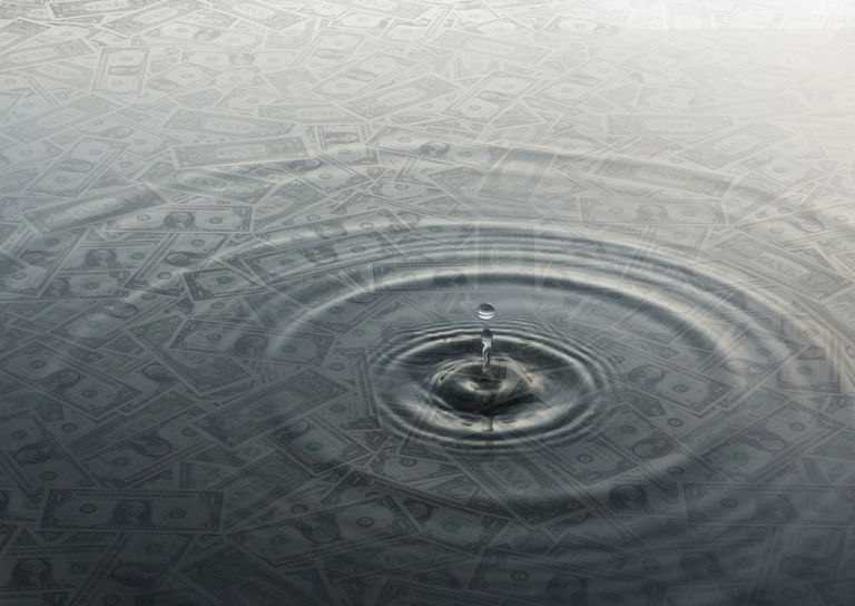 Ripple of water over dollar bills
