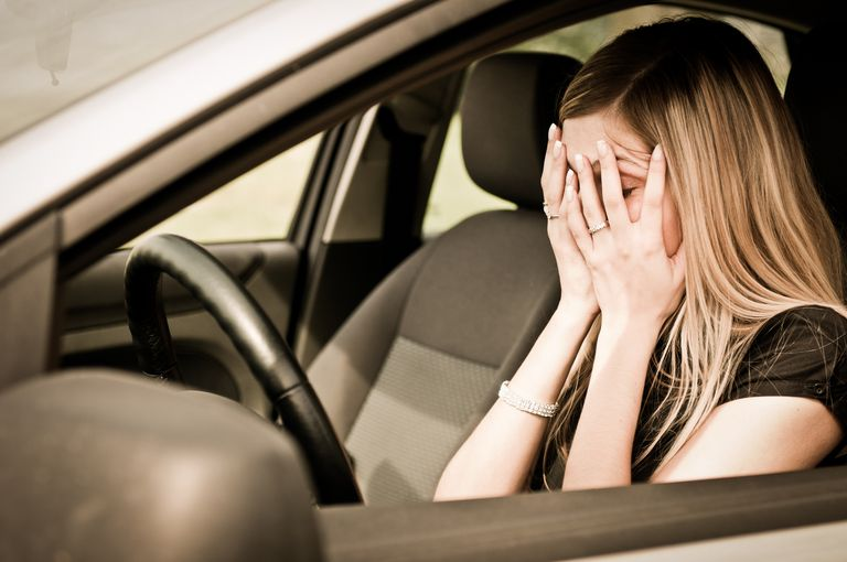 young woman in her car feeling panicky