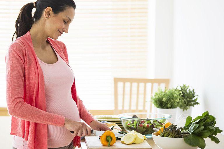 Pregnant woman making salad