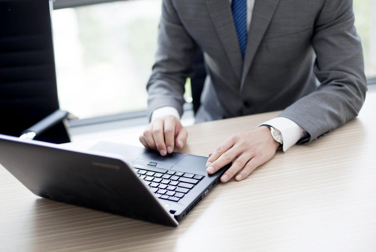 Picture of a businessman working on a laptop in an office