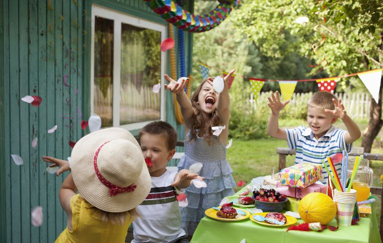 spring party for kids - kids laughing at table with flower petals in the air