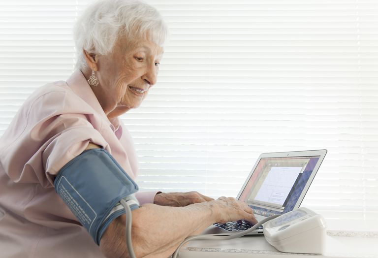 Elderly woman using blood pressure machine connected to her laptop