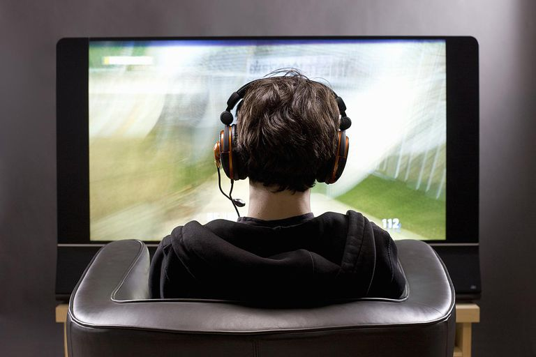 Teenager (15 years) sitting in chair shot from behind in studio playing video game on flat screen TV New York USA.