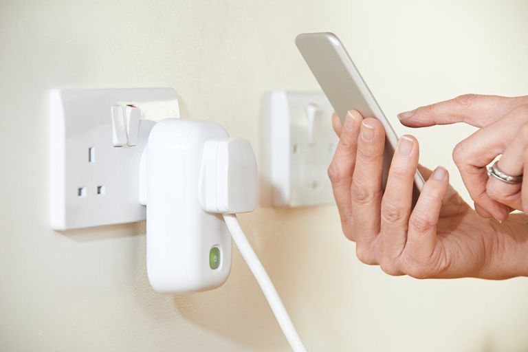 Woman controlling wi-fi smart plug with her smartphone