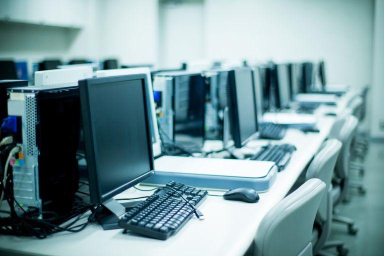 A long desk of desktop PCs