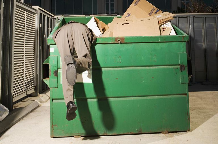 Businessman Searching Through Garbage Container