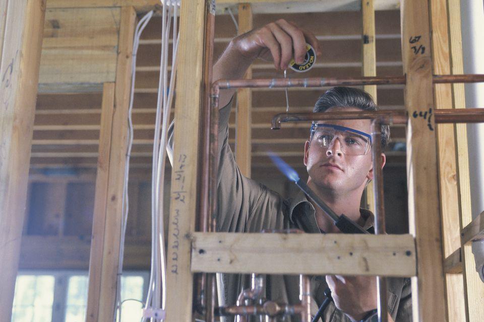 Plumber soldering pipes
