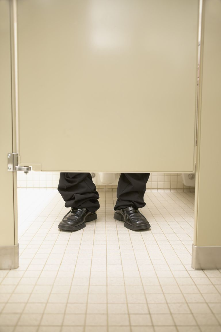Person's feet behind a closed door of a toilet cubicle