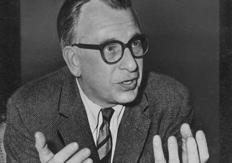 American architect Eero Saarinen, eyeglasses, gesturing with hands, talking, seated at desk