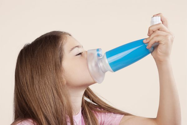 Girl using an asthma inhaler attached with spacer