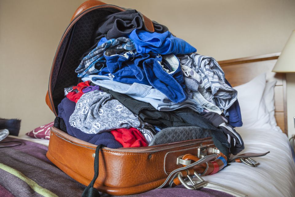A family's suitcase in a hotel bedroom