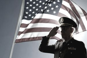 Silhouette of veteran US Army Colonel Chaplain wearing hat and saluting with an American flag flying behind him