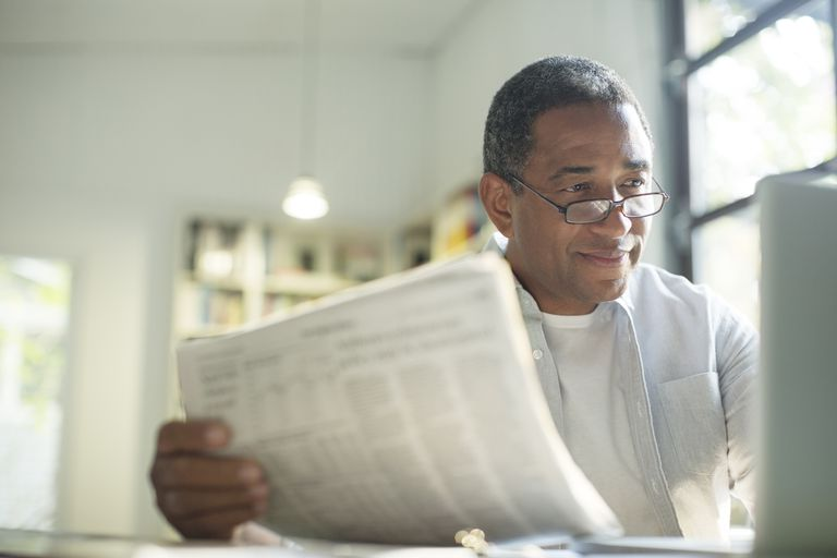 Man reading newspaper while looking at computer