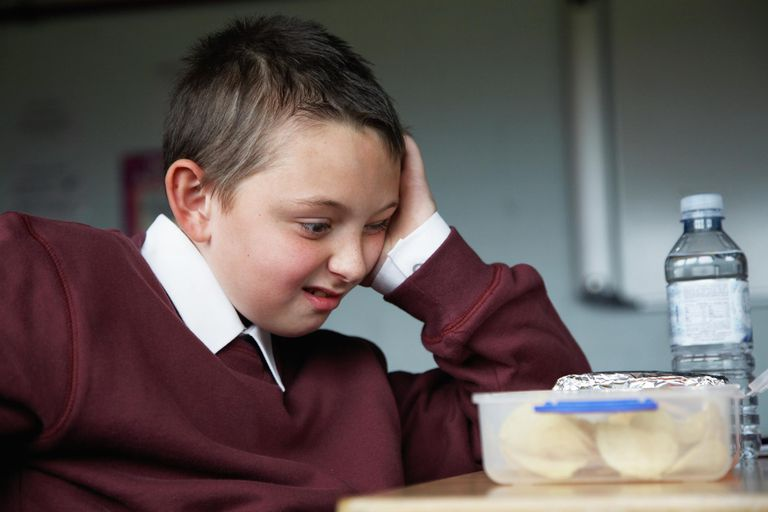 Schoolboy (8-10) sitting at desk staring at lunchbox, pulling face.