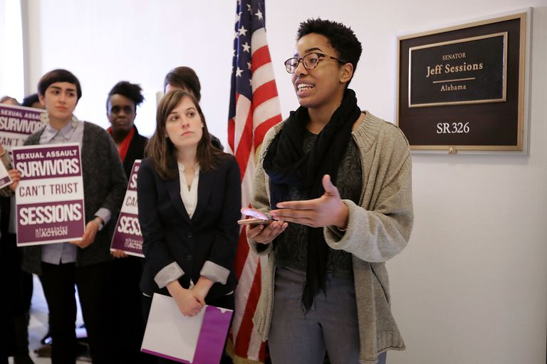 """Survivors of sexual assault protest the nomination of Senator Jeff Sessions to the position of U.S. Attorney General because he claimed that President Donald Trump's self-described behavior of grabbing women """"by the pussy"""" would not constitute sexual assault. Trump's words, actions, and Sessions' response to them are all evidence of rape culture."""