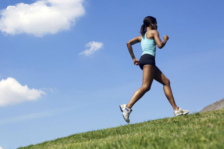 A female runner jogging up a hill outdoors.