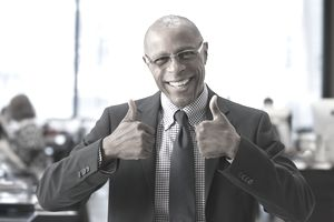 Businessman giving thumbs up in office