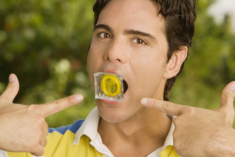 a young man holding a condom in his mouth