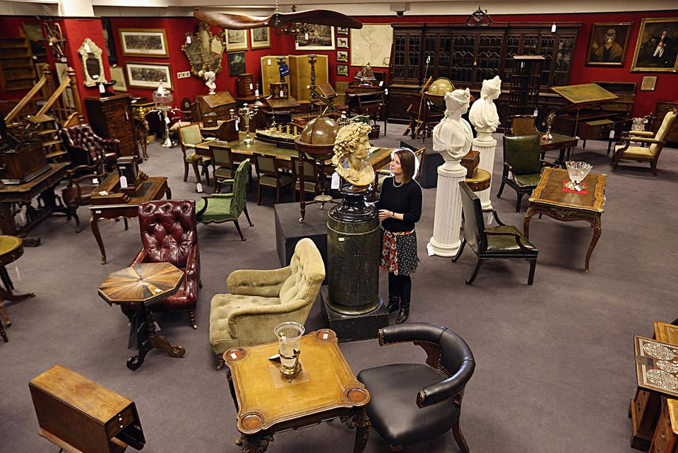 LONDON, ENGLAND - JANUARY 24: A gallery assistant at Bonhams auction house admires the lots for sale